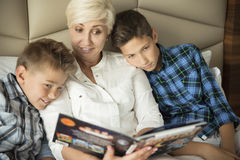 Reading mother and two sons stock image