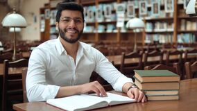 Reading with Music. Attractive asian student reading book with music, happy boy with stylish haircut wearing white headphones and glasses, indoor shot in well stock video