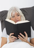 Reading a nail-biting book Royalty Free Stock Image
