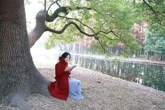 Reading in nature is my hobby, girl Read  book sit under big tree Royalty Free Stock Photos