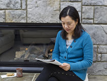 Reading near the Fireplace Royalty Free Stock Images