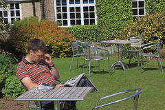 Reading The News. Young man reading the morning papers in the garden of a country hotel Royalty Free Stock Photography