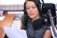 Reading news. A radio DJ reads news in the broadcasting studio royalty free stock photography