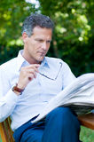 Reading news. Handsome mature man reading news outdoor during a break, while holding a pair of glasses Stock Image
