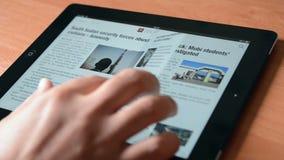 Reading news on an Apple iPad New Royalty Free Stock Photo