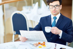 Reading news by breakfast Royalty Free Stock Image