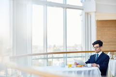 Reading news in cafe. Serious man in suit sitting in cafe and reading news Stock Photos