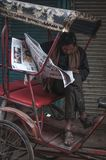 Reading the news. Old Delhi, India : February 15th, 2015 - A shot of a person reading a newspaper on his tricycle Royalty Free Stock Image