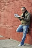 Reading a newspaper. This is a picture of a man leaning against a wall while reading a newspaper Stock Image