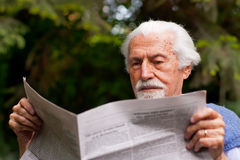 Reading the newspaper. Elderly man reading the newspaper  outdoors Stock Images