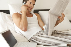 Reading Newspaper in Bed Stock Image