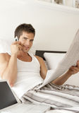 Reading Newspaper in Bed Stock Photography