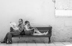 Reading newspaper on the bench Stock Image