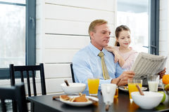 Reading Newspaper at Breakfast Stock Images