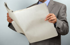 Reading the newspaper. Businessman holding and reading a blank newspaper with copy space Stock Photography
