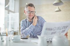 Reading newspaper. Confident businessman in eyeglasses talking on cellphone while reading newspaper Royalty Free Stock Photo
