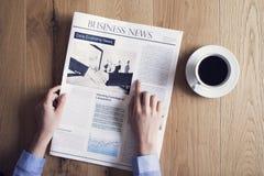 Reading newspaper on desk Stock Images