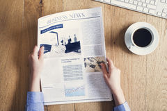 Reading newspaper on desk Royalty Free Stock Images