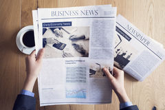 Reading newspaper on desk Royalty Free Stock Photography