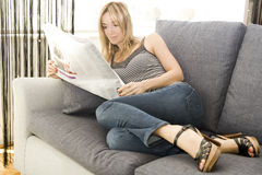 Reading newspaper on her flat Royalty Free Stock Photography