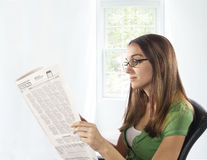 Reading newspaper at home in chair. Royalty Free Stock Images