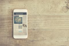 Reading newspaper from internet mobilephone wooden background. Reading newspaper from  internet mobilephone wooden background Stock Photos