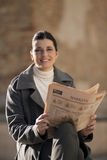 Reading newspaper outdoors. Young businesswoman reading newspaper outdoors Royalty Free Stock Images