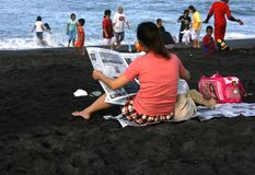 Reading a newspaper sitting beach Stock Photos