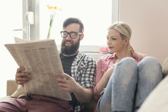 Reading newspaper. Young couple in love sitting on a couch in their apartment next to the window, enjoying their free time, reading newspaper and drinking coffee royalty free stock photos