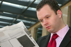 Reading newspapers. Young businessman reading blank newspapers Royalty Free Stock Image