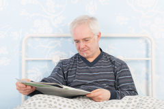 Reading newspapers in bed Stock Photography