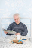 Reading newspapers in bed Royalty Free Stock Image