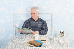 Reading newspapers in bed Royalty Free Stock Photo