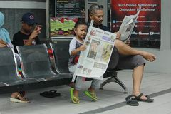 Reading Newspapers Like Father. 26/11/2017, Central Java, A child looks seriously reading a newspaper beside his father who is also seriously reading the Royalty Free Stock Image