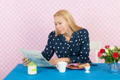 Reading newspapers in the morning. Mature woman reading newspapers in the morning while having breakfast Stock Photos