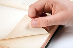 Reading the next page. Female hand turning a page of an old book royalty free stock photos