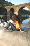 Reading next to a river Stock Photo
