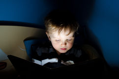 Reading at night. Child during reading book in his room at night Royalty Free Stock Images