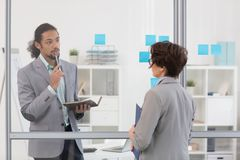 Reading notes on board. Two colleagues standing by transparent noticeboard with notepapers in office opposite one another Royalty Free Stock Image