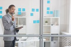 Reading notes. Pensive businessman with open notebook standing by transparent noteboard in office Stock Image