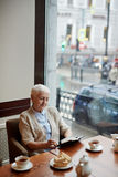 Reading notes. Senior author reading her notes while having brunch in cafe Stock Photography