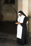 Reading nun in habit. Nun in habit reading the bible in a medieval church stock photo