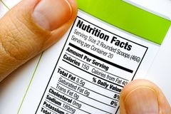 Reading nutrition facts on protein jar. Woman fingers with protein jar. Reading nutrition facts. Closeup Stock Photo