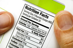 Reading nutrition facts on protein jar. Woman fingers with protein jar. Reading nutrition facts.  Close-up Stock Photography