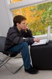 Reading online humor. Teen male working with a notebook computer with fall foliage visable through a large window Stock Images