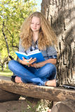 Reading outdoors. Beautiful young female student with book under the tree Stock Photo