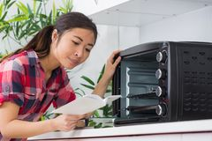 Reading the oven manual. Read Royalty Free Stock Photo