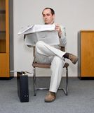 Reading the papers. Businessman waiting and reading the papers Royalty Free Stock Image