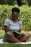 Reading in the park. Young african american woman sits and reads in the park stock photos
