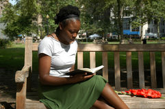 Reading in the park. Young woman sits on a bench in a park and reads royalty free stock photo